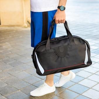 Młody człowiek trzyma torbę czarny sport z bliska