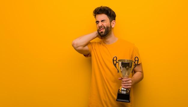 Młody człowiek trzyma trofeum cierpi ból szyi