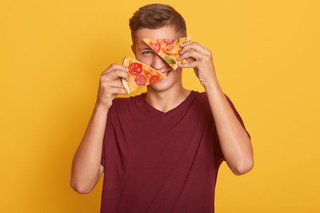 Młody człowiek trzyma w rękach dwa kawałki pysznej pizzy i zakrywa oczy pysznym produktem