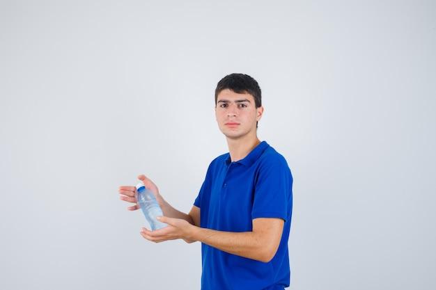 Młody człowiek trzyma w rękach plastikową butelkę w t-shirt i wygląda pewnie, widok z przodu.
