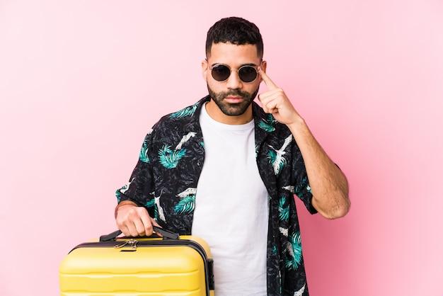Młody człowiek trzyma walizkę wskazując palcem świątynię, myśląc, skupiony na zadaniu