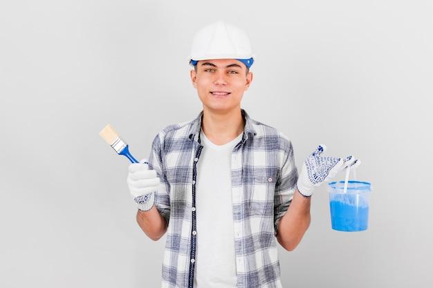 Młody człowiek trzyma wiadro pędzla i farby