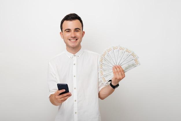Młody człowiek trzyma wiązkę dolarów i jego mądrze telefon. bankowość mobilna. zakłady online.