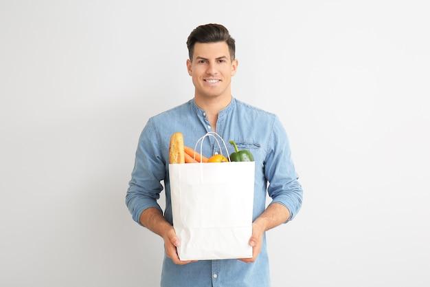 Młody człowiek trzyma worek z jedzeniem na jasnym tle