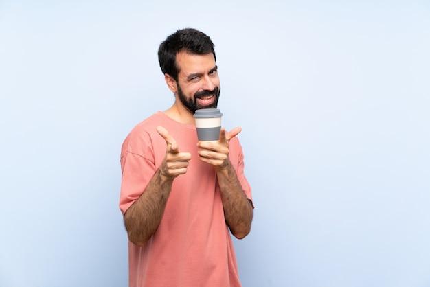 Młody człowiek trzyma zabierającą kawę nad odosobnioną błękit ścianą z brodą wskazuje przód i ono uśmiecha się