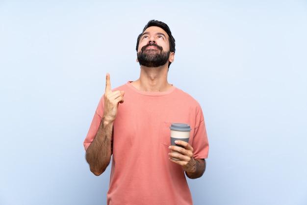 Młody człowiek trzyma zabraną kawę nad odosobnioną błękit ścianą z brodą wskazuje w górę i zaskakujący