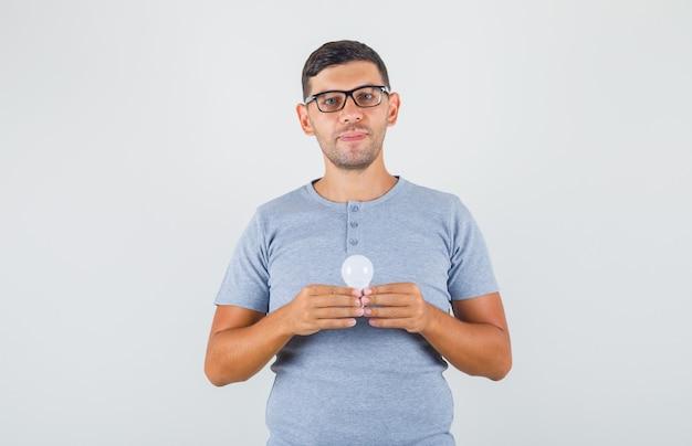 Młody człowiek trzyma żarówkę i uśmiecha się w szarej koszulce