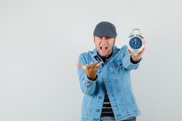 Młody człowiek trzyma zegar, podnosząc rękę w agresywny sposób w kurtce, czapce i patrząc zły. miejsce na tekst