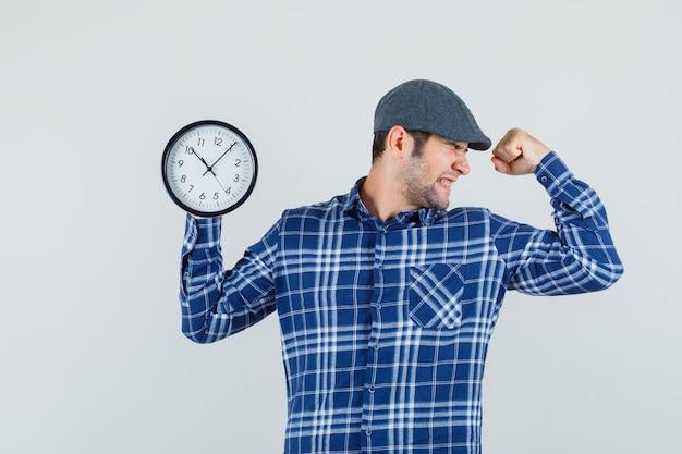 Młody człowiek trzyma zegar ścienny w koszuli, czapce i wygląda błogo. przedni widok.