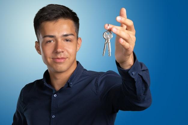 Młody człowiek trzyma zestaw kluczy do domu