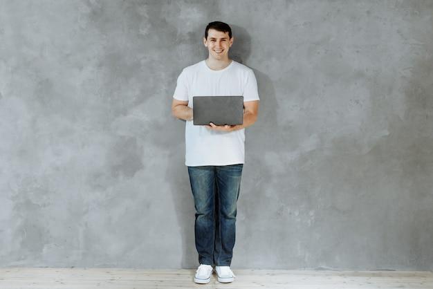 Młody człowiek trzymając laptopa i wpisując stojąc na szarym tle