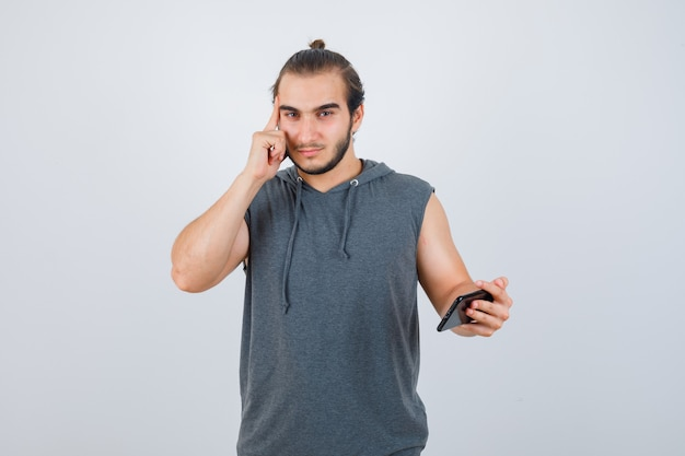 Młody człowiek, trzymając palce na skroniach w t-shirt z kapturem i patrząc zamyślony, widok z przodu.