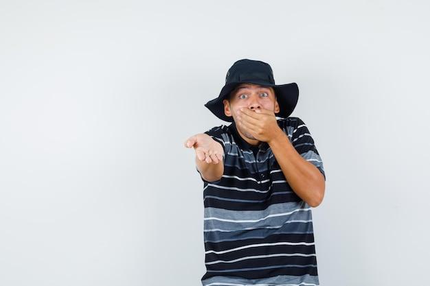 Młody człowiek trzymając rękę na ustach w koszulce, kapeluszu i patrząc przestraszony. przedni widok.