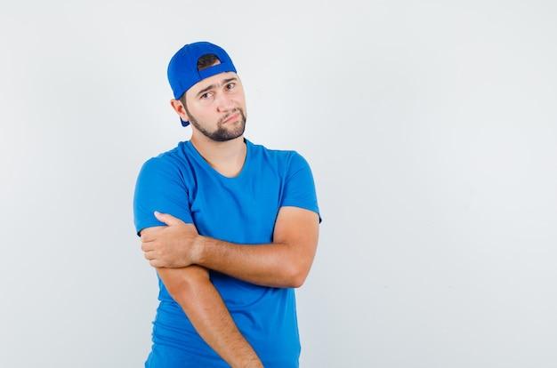 Młody człowiek trzymając rękę z ręką w niebieskiej koszulce i czapce i patrząc zamyślony