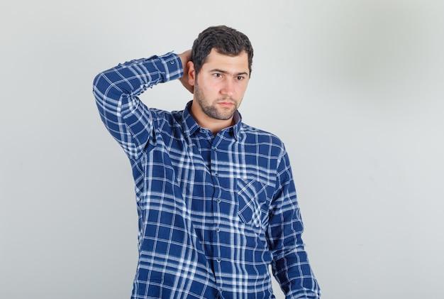 Młody człowiek trzymając rękę za głową w kraciastej koszuli i patrząc zamyślony