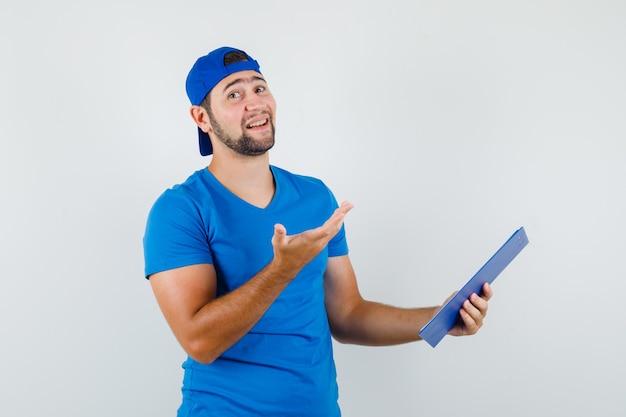 Młody człowiek trzymając schowek i podnosząc rękę w niebieskiej koszulce i czapce i patrząc wesoło