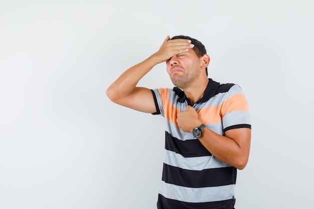 Młody człowiek, trzymając się za ręce na czole i klatce piersiowej w t-shirt i źle wyglądający