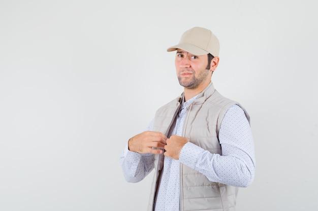 Młody człowiek, trzymając się za ręce na kołnierzu w koszuli, kurtce bez rękawów, czapce i wyglądający fajnie, widok z przodu.