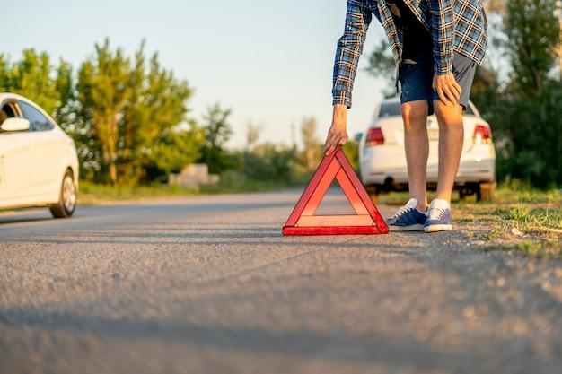 Młody człowiek trzymający czerwony trójkąt i umieścił go na drodze, znak wypadku samochodowego