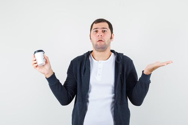 Młody człowiek trzymający filiżankę kawy na wynos i pokazujący bezradny gest kciuka w białej koszulce i czarnej bluzie z kapturem na zamek błyskawiczny i wyglądający poważnie, widok z przodu.