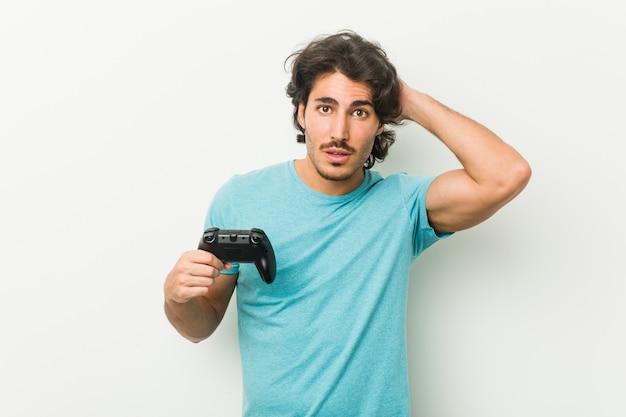 Młody człowiek trzymający kontroler gier jest w szoku, przypomniała sobie ważne spotkanie.