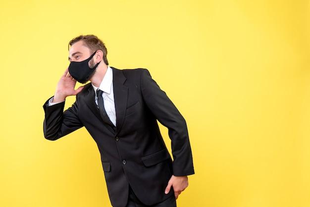 Młody człowiek trzymający rękę przy uchu i uważnie słuchając na żółto