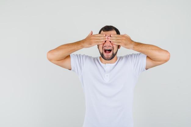 Młody człowiek trzymający się za ręce na oczach w t-shirt i patrząc nieśmiały, widok z przodu.