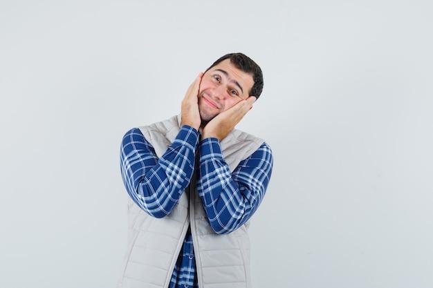 Młody człowiek trzymający się za ręce na twarzy, pochylając głowę w koszuli, kurtce bez rękawów i wyglądając na spokojnego. przedni widok.