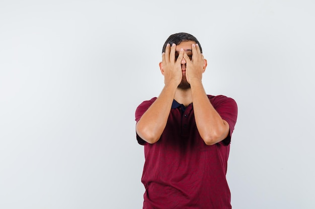 Młody człowiek trzymający się za ręce na twarzy w t-shirt i patrząc na zmęczonego. przedni widok.