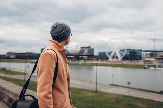Młody człowiek turystyczny spacer wzdłuż molo nad wisłą w krakowie, polska, podziwiając krajobraz diabelski młyn.