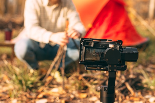 Młody człowiek tworzy blog wideo o życiu obozowym i ognisku.