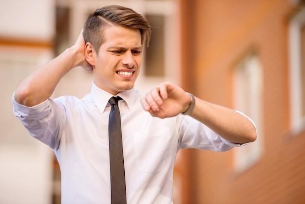 Młody człowiek ubrany formalnie patrząc na zegarek spóźniony.