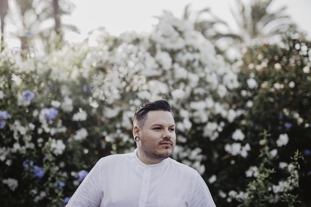 Młody człowiek ubrany w białą koszulę i kwiaty na tle