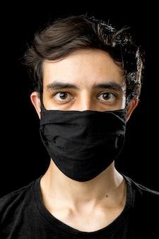 Młody człowiek ubrany w czarną maskę. koncepcja okresu kwarantanny koronawirusa covid-19 pandemii.
