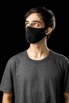 Młody człowiek ubrany w czarną maskę. patrząc w górę. koncepcja okresu kwarantanny koronawirusa covid-19 pandemii.