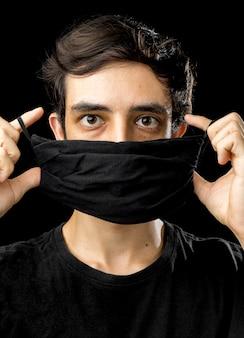 Młody człowiek ubrany w czarną maskę.