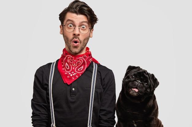 Młody człowiek ubrany w czerwoną chustkę i czarną koszulę i jego psa