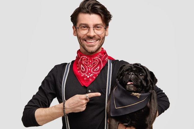 Młody człowiek ubrany w czerwoną chustkę i czarną koszulę trzyma psa