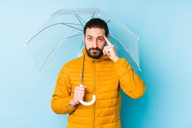 Młody człowiek ubrany w długie włosy wygląd trzyma parasol izolowany wskazując świątynię palcem, myśląc, skupiony na zadaniu.
