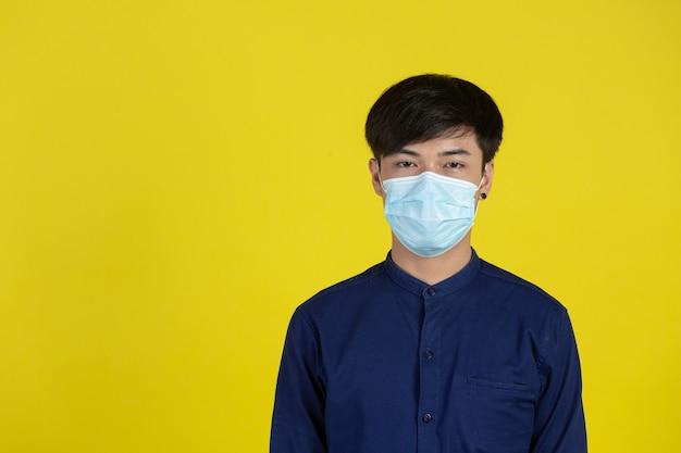 Młody człowiek ubrany w jednorazową maskę medyczną stojący przed żółtą ścianą