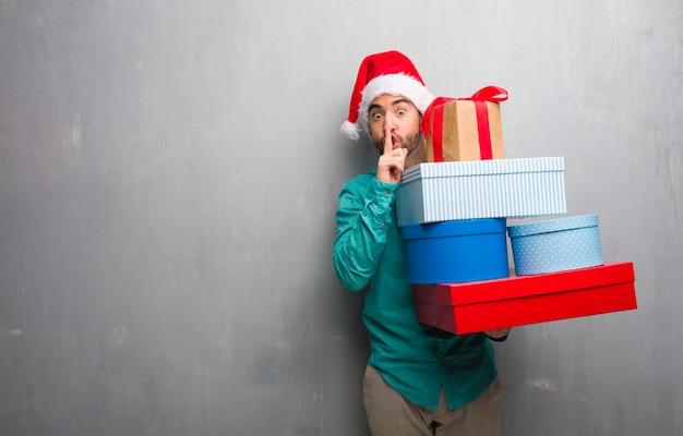 Młody człowiek ubrany w kapelusz santa gospodarstwa prezenty utrzymanie w tajemnicy lub z prośbą o ciszę