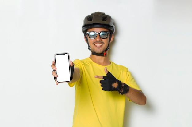 Młody człowiek ubrany w kask rowerzysty trzyma telefon komórkowy z pustym pustym ekranem na białym tle