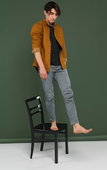 Młody człowiek ubrany w koszulę, pozowanie na krześle