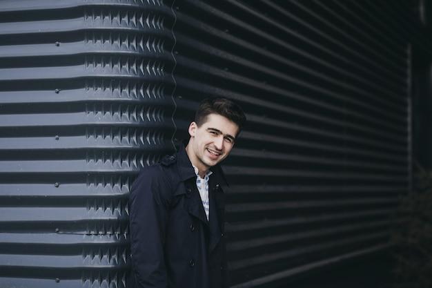 Młody człowiek ubrany w kurtkę i uśmiech przeciw ścianie