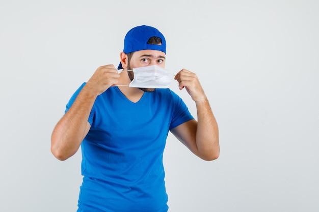 Młody człowiek ubrany w maskę medyczną w niebieskiej koszulce i czapce i patrząc ostrożnie