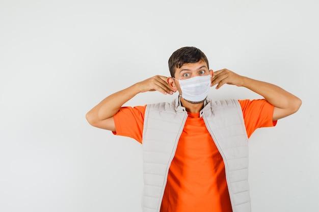 Młody człowiek ubrany w maskę medyczną w t-shirt, kurtka