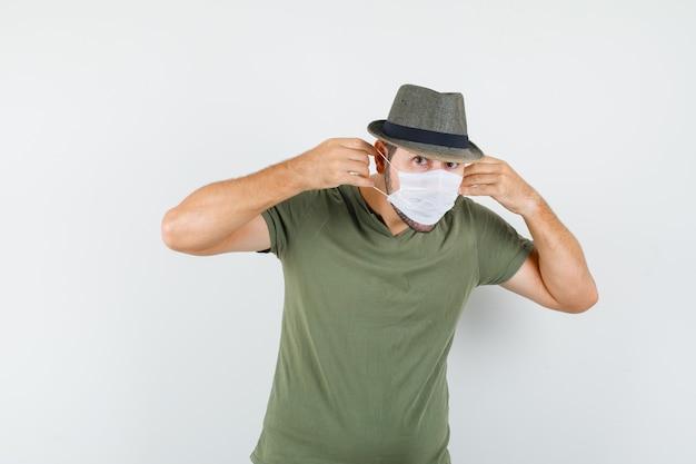 Młody człowiek ubrany w maskę medyczną w zielonej koszulce i kapeluszu i patrząc poważnie