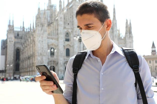 Młody człowiek ubrany w maskę ochronną za pomocą aplikacji na smartfony w mediolanie we włoszech