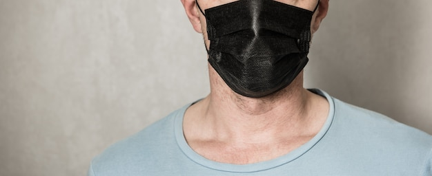 Młody człowiek ubrany w maskę. przystojny mężczyzna w czarnej bluzie z kapturem nosić czarną maskę medyczną, szare tło, miejsce. koncepcja okresu kwarantanny koronawirusa covid-19 pandemii