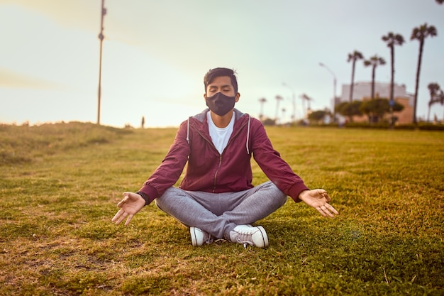 Młody człowiek ubrany w maskę w parku. sport na świeżym powietrzu o zachodzie słońca. joga w parku